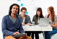 Handsome young ethnic male with dreadlocks holding a tablet and looking at the camera with his colleagues sitting in the background