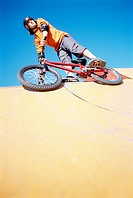 A BMX rider with his bicycle at the skate park