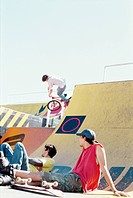 Two young men taking a break at the skate park watching a biker do a stunt