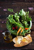 Spring vegetables in a green pot with white bread and a small jug of olive oil