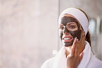 Portrait of a woman applying a face mask