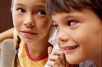 Close up portrait of two children listening on a phone together