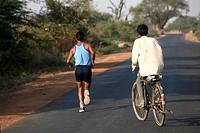 Athlete running on highway followed by cyclist in Bhopal ; Madhya Pradesh ; India