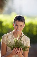 Portrait of a woman posing for the camera with a bunch of herbs