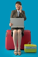 Businesswoman Waiting for Flight Using Laptop and Cell Phone