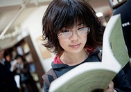 Asian young woman reading in a library