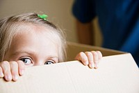 Young Girl Peeking Out of a Cardboard Box