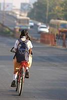 School girl riding on bicycle , Nagpur , Maharashtra , India