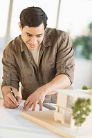 Male architect working with blueprint and model home
