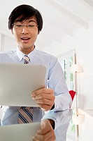 Young Asian businessman communicating on his Tablet computer