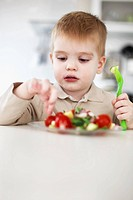 Boy picking at plate of fruit in kitchen