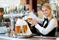 Female bartender pouring beer