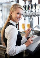 Young waitress using computer at restaurant counter