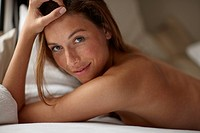 Smiling nude woman laying on bed