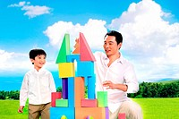 Boy playing toy bricks with his father