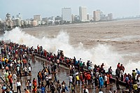 People enjoying hightide waves at marine drive Bombay , Mumbai , Maharashtra , India NOMR