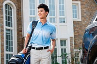 A young man standing in front of villa with golf bag
