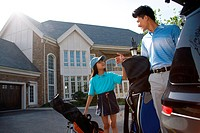 Oriental father and daughter standing by car with golf bag in front of villa