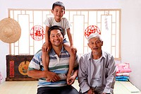 Boy with his grandfather and father at home
