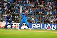 Indian captain, batsman M S Dhoni plays his shot watched by Sri Lankan captain, wicketkeeper during the 2011 ICC World Cup Final between India and Sri...