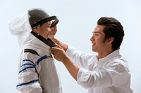 Young man help boy wearing spacesuit