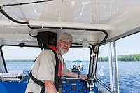 Public works engineer piloting service boat for sampling water on public reservoir