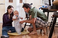Parents changing their son´s clothes together while sitting on the floor