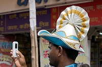 Man wearing Japanese fan like headgear and taking photo Pune Maharashtra India Asia Sept 2011