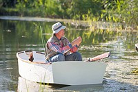 Senior man preparing to fish on sunny lake