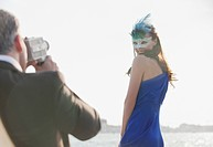 Man filming woman with mask at waterfront in Venice