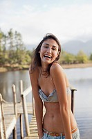 Portrait of enthusiastic woman in bikini at lakeside