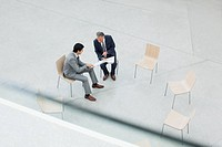 Businessmen reviewing paperwork in circle of chairs