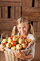 Portrait of smiling girl holding bushel of apples