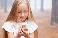 Close up of girl holding butterfly in woods