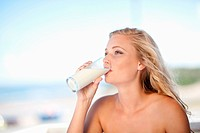 Woman drinking glass of milk outdoors