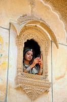 Rajasthani lady using mobile standing at jharokha of Nathmal haveli ; Jaisalmer ; Rajasthan ; India MR