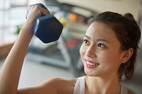 Chinese woman lifting weights in gym