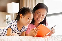 Chinese mother and daughter reading together