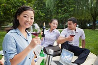 Chinese business people drinking wine in park