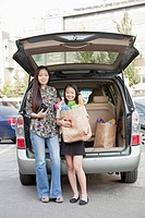 Chinese mother and daughter unloading groceries from car