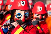 Traditional flute players in a vibrant red firefighter´s costume with black and white Basel coat of arms on their helmets