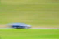 Blurred motion of one car travelling on road in green landscape