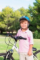 Happy little boy wearing a helmet with his bike