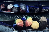 Venice  Italy  Gondolas packed with tourists holding umbrellas in the pouring rain