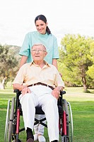 Nurse pushing elderly man through the park