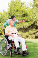 Nurse pointing to something with man in wheelchair