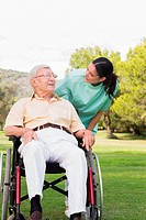 Nurse chatting with man in wheelchair