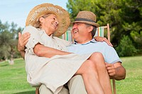 Woman sitting on lap of partner sitting in deck chair and smiling at him