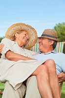 Happy woman sitting on lap of partner sitting in deck chair