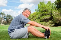 Smiling mature man stretching in the park